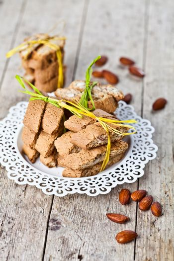 Fresh Italian cookies cantuccini stacked on white plate and almonds on ructic wooden table background.