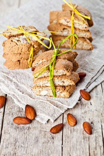 Fresh Italian cookies cantuccini stacks and almond nuts on linen napkin on ructic wooden table background.