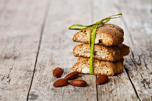 Fresh Italian cookies cantuccini stack and almond nuts on ructic wooden table background.