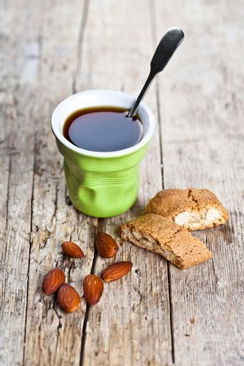 Cup of coffee, fresh Italian cookies cantuccini and almond nuts on ructic wooden table background.