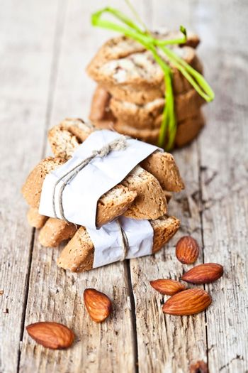 Fresh Italian cookies cantuccini stackes and almond nuts on ructic wooden table background.
