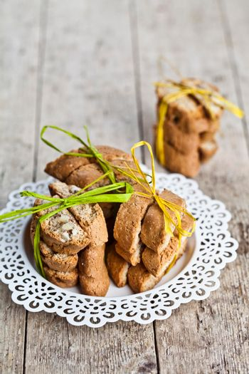 Fresh homemade Italian cookies cantuccini stacked on white plate on ructic wooden table background.