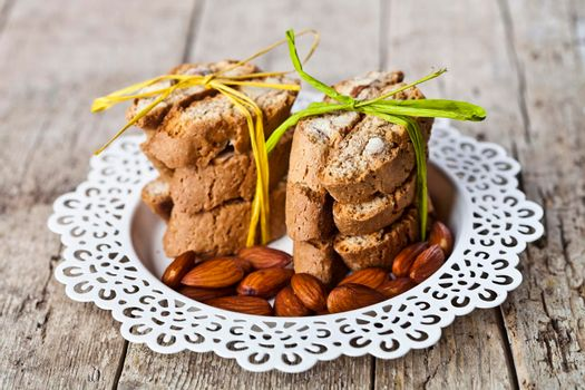 Almond seeds and fresh Italian cookies cantuccini stacked on white plate on ructic wooden table background.