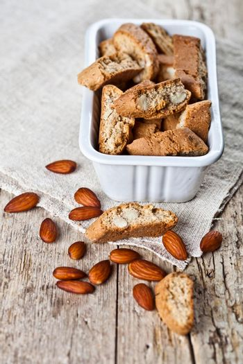 Cookies cantuccini in white ceramic bowl and almond seeds on linen napkin closeup on ructic wooden table background.