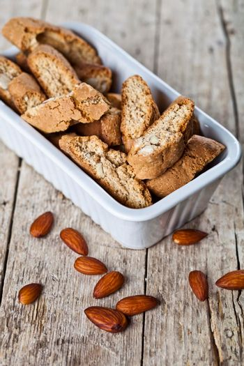Cookies cantuccini with almond seeds  in white ceramic bowl closeup on ructic wooden table background.