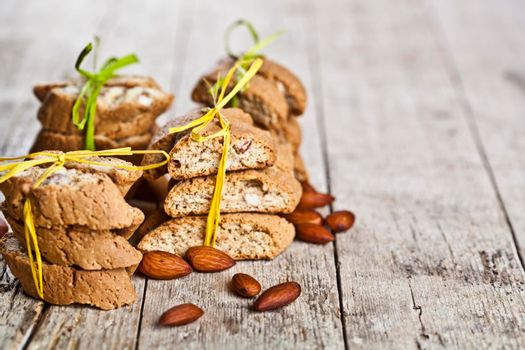 Fresh Italian cookies cantuccini stackes and almond seeds on ructic wooden table background.