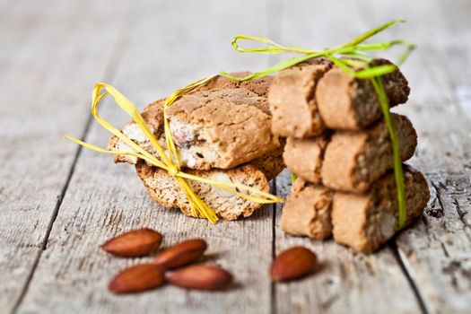 Fresh Italian cookies cantuccini stacks and almond seeds on ructic wooden table background.