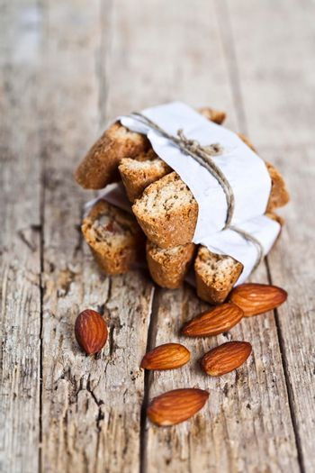 Fresh homemade Italian cookies cantuccini stackes and almond seeds on ructic wooden table background.