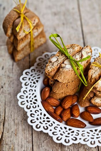 Fresh Italian cookies cantuccini stacked and almond seeds  on white plate closeup on ructic wooden table background.