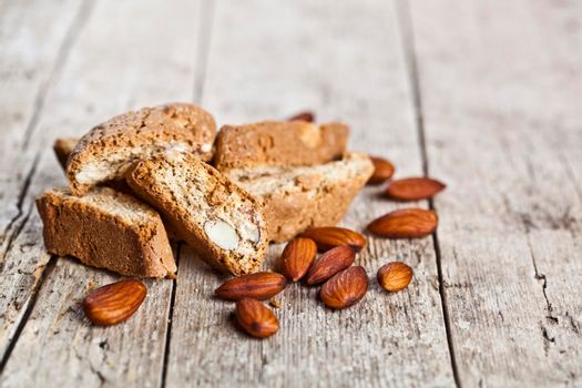 Fresh homemade Italian cookies cantuccini heap and almond seeds on ructic wooden table background.