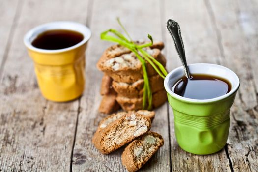Two cups of coffee, fresh Italian cookies cantuccini and almond seeds on ructic wooden table background.