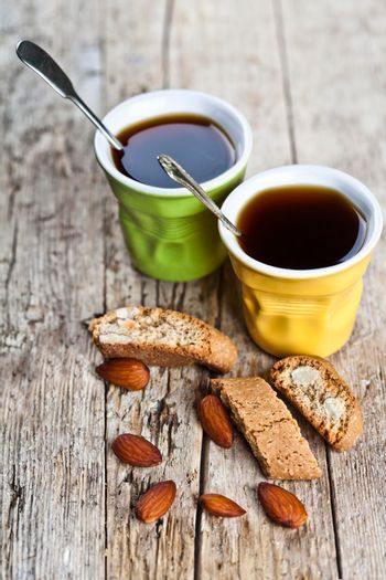 Two cups of coffee and fresh Italian cookies cantuccini with almond nuts on ructic wooden table background.