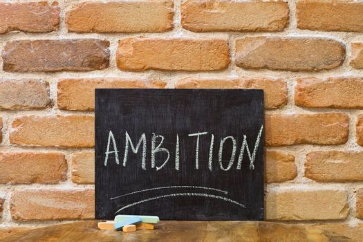 Chalk board with the word AMBITION drown by hand and chalks on wooden table on brick wall background.