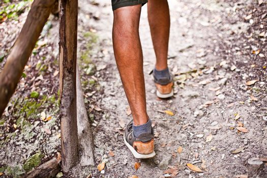 Man's legs on park or forest footpath with handrail closeup.