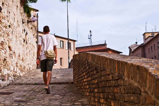 Back view of a man tourist walking in ancient town.