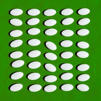 White pills on green background.