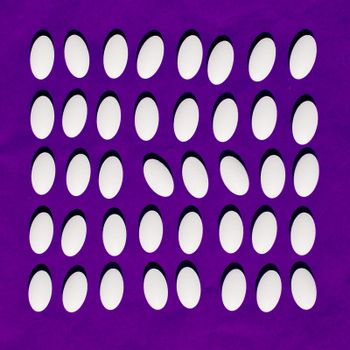 White pills on purple background.