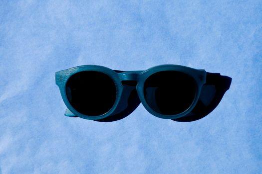 Stylish sunglasses with shadow on blue background.