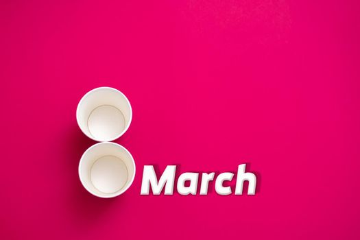 Two an empty paper cups in form of the number 8. On a red background. The inscription is March 8. The concept of congratulations on March 8. Layout. Copy space. Environmental material.