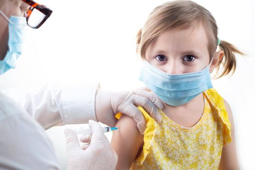 Vaccination concept in the era of coronavirus. Woman Doctor vaccinating cute little girl wearing yellow dress and facial protective mask on white background.