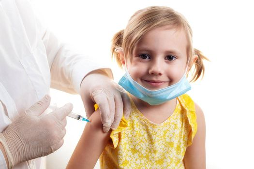 Vaccination concept in the era of coronavirus. Doctor vaccinating cute smiling little girl wearing yellow dress and facial protective mask on white background.