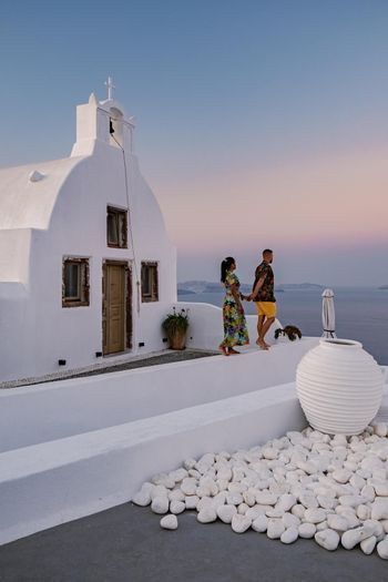 Santorini Greece, young couple mid age European and Asian on vacation at the Greek village of Oia Santorini Greece, luxury vacation Santorini. mid age man and woman watching sunset Santorini