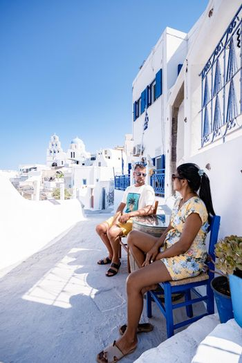 Pyrgos village Santorini with blue domes and white washed house during sunset at the Island of Santorini Greece Europe, sunrise Santorini, young couple mid age men and woman visit Pyrgos Santorini