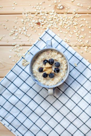 Fresh porridge with berries in a plate on a napkin. A fresh and healthy breakfast.