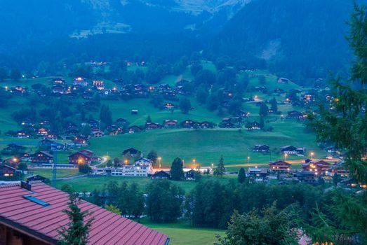 The village of Grindelwald below the summit of wetterhorn after sunset, Berner Oberland Swiss Alps Switzerland