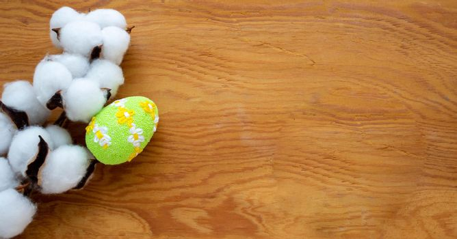 Dried white fluffy cotton flower and green egg on wooden background, close-up, copy space, top view. The concept of Easter.