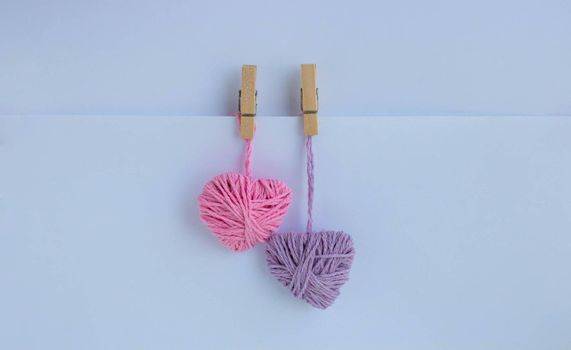 Two hearts of thread hang with clothespins on a paper pocket. Holiday card, background. The concept of Valentine's Day, March 8, Mother's Day.