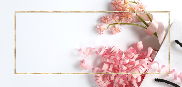 Pink spring flowers, pink gift streamer in white gift bag on white background. Beautiful spring card for Birthday, Woman, Valentines, Mothers Day in pastel colours. Horizontal flat lay. Copy space