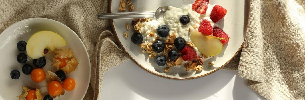 Healthy breakfast yogurt bowl with granola and berries. Rustic backgroundwith morning sun light. Concept of clean eating, dieting and weight loss. Horizontal top view, flat lay