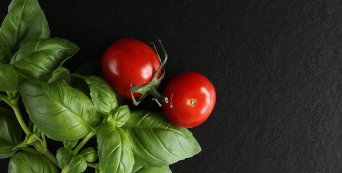 Fresh cherry tomatoes on black background, green basil. Top view, copy space
