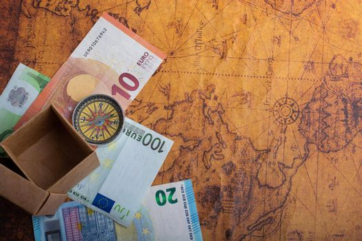 Compass,  box and Euro banknotes  on map as business concept