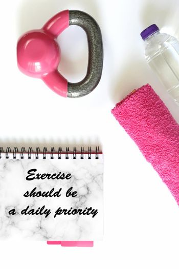 Fitness motivational quote. Healthy lifestyle, fitness, sport, athlete's equipment in pink colour on white background. Quote text Exercise should be a daily priority. Copy space, mock up