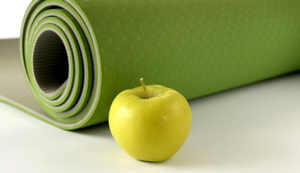 Yoga fitness, health life style. Yoga rolled green mat and green apple on white background. Place for text. Healthy lifestyle, fitness, sport concept