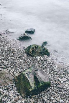 Row of boulders in foam of waves