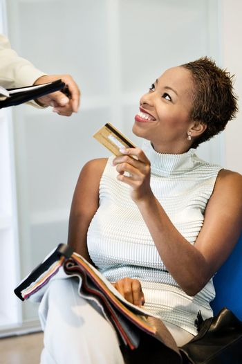 Portrait of african american woman making purchase on credit card