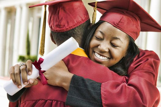 Portrait of woman hugging boyfriend after graduation