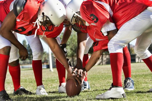 Portrait of Football Players in Huddle Holding Football