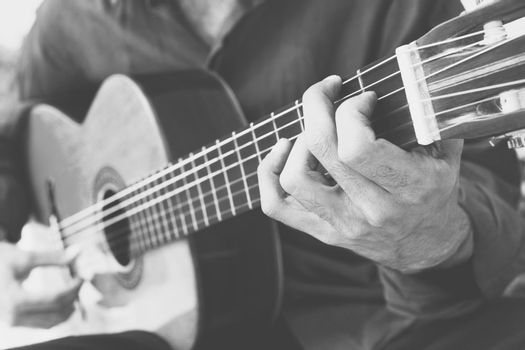 Black and white photo of man playing acoustic guitar