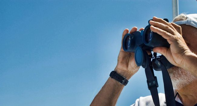 Captain of Racing Yacht Using Binoculars