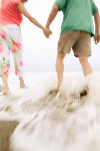 Photo of mid adult couple walking on the beach