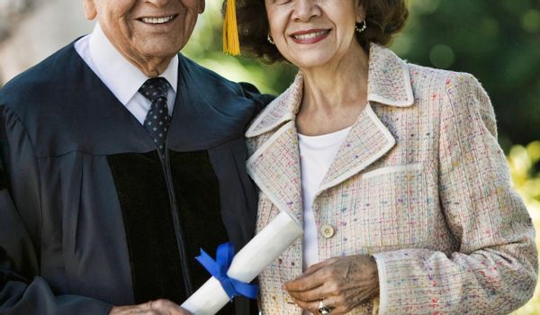 Senior Graduate holding diploma with his Wife