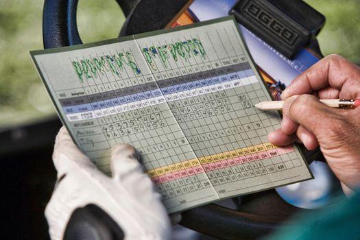 Golfer Marking Score on Scorecard