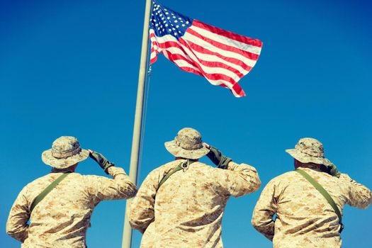 Rear view of Soldiers Saluting American Flag