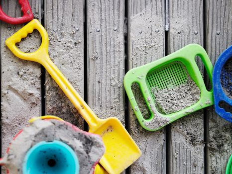 Sand pit toys lying on wooden deck