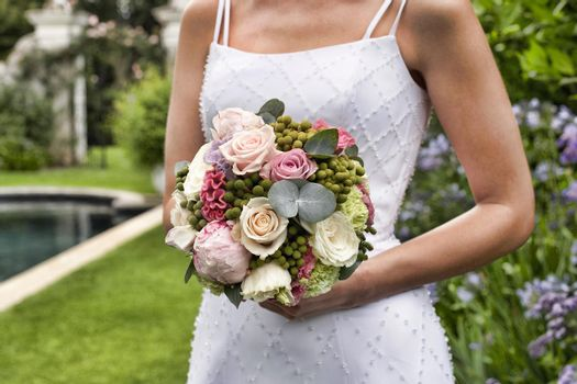 Young bride holding bouquet in formal garden