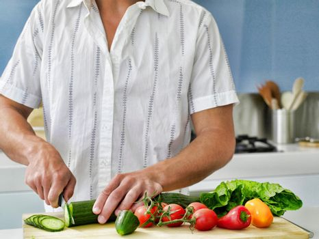 Midsection of young man cutting vegetables on wooden board in domestic kitchen